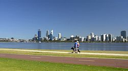 Various people exercising along the Swan River, walking, and cycling, with Perth City in the background.