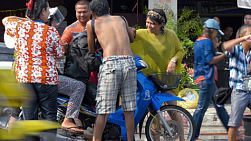 Bangkok, Thailand - April 14, 2014: Two people on a motorbike getting splashed with water on the side of a busy road, as part of a water fight during the Songkran Festival in Thailand.