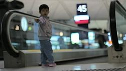 People and families step onto a people mover at a large international airport in Hong Kong.