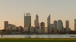 People exercising along the South Perth foreshore, with the Perth city skyline and the Swan River in the background at dusk.