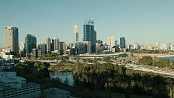Looking down on the City of Perth skyline, freeway with trees and water, as seen from King's Park in Western Australia.