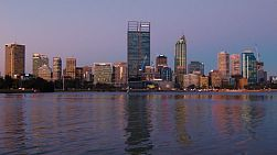 View of the City of Perth from across the Swan River, with the reflections on the water, in the purple post sunset light on a clear spring evening.