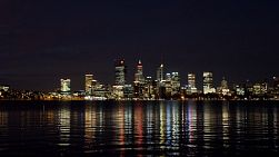 Perth, Australia - February 2020: Time lapse of the Perth city skyline at night, with the CBD lights reflecting on the surface of the Swan River.
