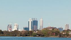 View of the Perth City skyline framed between trees lining the banks of the Swan River and clear blue skies above.