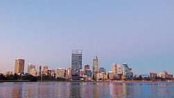 The lights of the Perth City Skyline are shining in the fading light of dusk, framed by clear skies above and the reflections on the Swan River below.