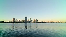 Time lapse of a wide angle view of the Perth CBD skyline from across the Swan River, as dusk settles and the light fades.
