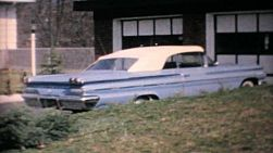 A cool 1960 Pontiac Parisienne convertible parked in front of a lovely home in the suburbs in 1964.