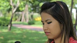 A pretty Thai girl answers her cell phone to talk to a friend at the park in Bangkok, Thailand.