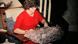 A pretty young girl in a red dress opens her Christmas gifts in 1957.