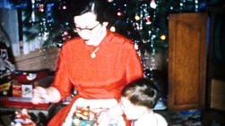 A pretty mother spends time with her family opening gifts and celebrating Christmas in Cleveland, Ohio in 1956.