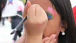 A cute 10 year old Thai girl gets a princess crown painted on her face at the summer carnival.