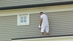 A professional house painter paints a townhouse in a residential area.