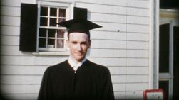 A proud college graduate poses for picture in the front yard before the commencement service in 1960.