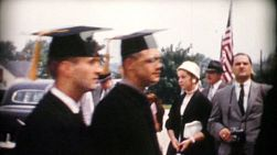 Proud family members watch college graduates walking by on their way to the commencement service in 1960.