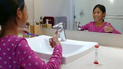 A cute little 9 year old Asian girl uses an egg timer to help her brush her teeth longer.