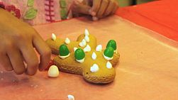 A little girl makes a deliciously sweet looking Gingerbread Man cookie for Christmas.