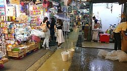 Rain pours into the famous Chatuchak weekend market in Bangkok, Thailand as tourists and vendors run for cover.