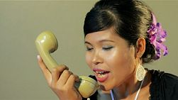 Young asian woman answering the phone, getting mad and angry with a telemarketer, and hanging up in anger - tracking shot.