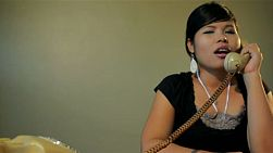Vintage style set of young asian woman answering the phone, getting mad and angry with a telemarketer, and hanging up in anger - tracking shot.