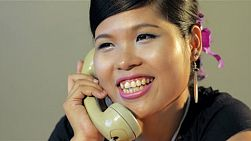 Retro young asian woman answering the phone - tracking shot into focus.