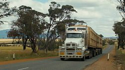 A road train travelling down a road in country Western Australia, with the Stirling Ranges in the background.