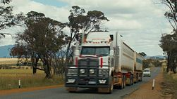 A road train travelling on a road in country Western Australia, with the Stirling Ranges in the background..