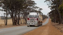 A road train with a load of freshly harvested grain driving down a rural road in Australia.