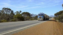 A road train driving down a highway in rural Australia, with the Stirling Ranges in the background.