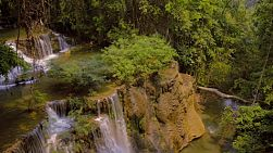 Looking down on a waterfall and the stream flowing into the jungle at the Huay Mae Khamin waterfalls in Kanchanaburi, Thailand.
