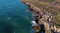 Aerial shot flying over rocky limestone coastline in Western Australia.