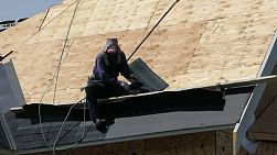 A roofing technician or roofer works hard on a hot summers day to finish shingling a new home in the suburbs of Vancouver, BC, Canada.