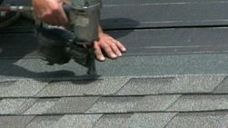 A man uses a nail gun to lay shingles on the roof of a new home.