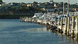 A row of yachts moored at a yacht club on the Swan River in Perth, Western Australia.