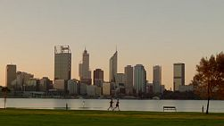 People jogging along the South Perth Foreshore, with a view of the Swan River and city skyline in the background.