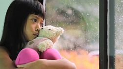 A sad little seven year old Asian girl sits by the window with her Teddy Bear watching the rain drops fall.