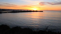 A beautiful sunrise comes up over the bay and wharf in Santa Cruz, California.