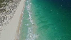 Aerial shot flying along the coast at Scarborough Beach, Perth, Western Australia, tilting up to reveal small waves washing ashore and the long sandy coastline stretching far into the background.