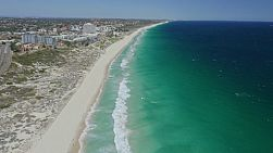 Aerial shot flying along the coast at Scarborough Beach, Perth, Western Australia, with small waves washing ashore and the long sandy coastline stretching far into the background.
