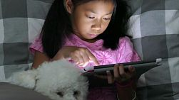 A cute little Asian girl uses her tablet alone in her bedroom at night with her faithful puppy at her side.