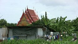 A shot of a run down shack in rural Thailand with a beautiful Buddhist temple in the background.