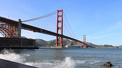 A ship passes under the famous iconic Golden Gate bridge in San Francisco, California.
