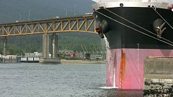 A large container ship purges water while sitting in port at Vancouver, BC. (HD 1080p30)