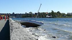 An abandoned shipwrecked sailboat rests on the rocky shore of English Bay in Vancouver, BC as curious onlookers come to check out the damage.
