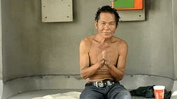 Rough looking beggar greeting with a 'wai', while on the streets of Bangkok, Thailand.