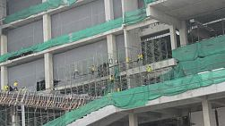 An exterior shot of workers working on a large shopping center construction work site in Bangkok, Thailand.