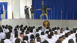 A group of young adults on a short term overseas missions trip have fun performing a drama during a large assembly in Ratchaburi, Thailand.