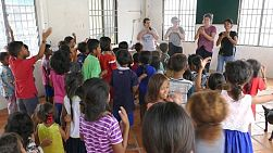 PHNOM PENH, CAMBODIA, JUNE 2018: A group of high school students on an overseas missions trip sing action songs to kids in a slum community in Phnom Penh.