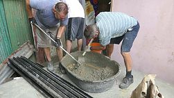 A group of young adults on a short term overseas missions trip have fun mixing wet cement by hand in the slums in Bangkok, Thailand.