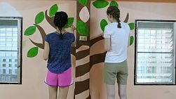 A group of high school students painting a wall mural in a kindergarten located in the slums in Bangkok, Thailand.