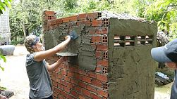 SVAY RIENG, CAMBODIA, JUNE 2018: A female young people on a short-term missions trip plasters the side of a new bathroom with cement on a service trip to Cambodia.